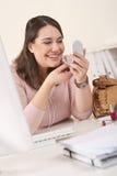 Mulher de negócios nova que aplica o batom no escritório Fotos de Stock