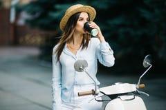 Mulher de negócios nova que bebe um café em um 'trotinette' italiano Mulher que está no 'trotinette' na rua foto de stock royalty free