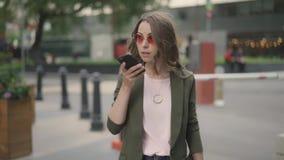 Mulher de negócios nova que disca um número e que fala o passeio na rua da cidade da queda filme
