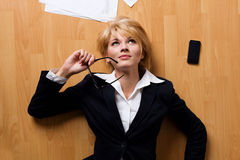 Mulher de negócios nova que encontra-se no assoalho Foto de Stock Royalty Free
