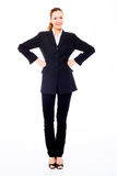 Mulher de negócios nova que está com os braços akimbo Fotografia de Stock Royalty Free