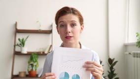 Mulher de negócios nova que fala fazendo a conferência de negócio a chamada video que discute o relatório vídeos de arquivo