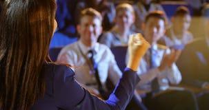 Mulher de negócios nova que fala na fase no auditório 4k filme