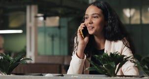Mulher de negócios nova que fala no telefone ao sentar-se no café Está sorrindo Menina bonita que tem ocasional video estoque