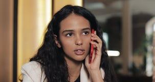 Mulher de negócios nova que fala no telefone ao sentar-se no café Está sorrindo Menina bonita que tem ocasional filme