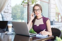 Mulher de negócios nova que fala no telefone no café foto de stock royalty free