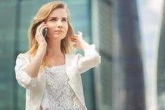 Mulher de negócios nova que fala no telefone celular ao andar exterior foto de stock