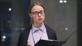 Mulher de negócios nova que faz anotações na prancheta na rua filme