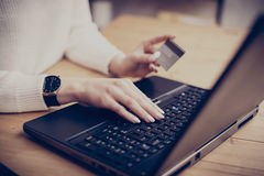 Mulher de negócios nova que faz a compra em linha através do portátil, datilografando no teclado e usando seu cartão de crédito H imagens de stock