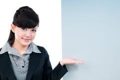 Mulher de negócios nova que gesticula no quadro de avisos em branco Fotografia de Stock Royalty Free