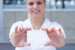 Mulher de negócios nova que guarda um cartão vazio foto de stock