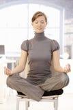 Mulher de negócios nova que meditating no escritório imagens de stock royalty free