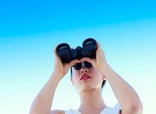 Mulher de negócios nova que olha através dos binóculos Imagem de Stock
