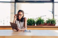 Mulher de negócios nova que olha na tabuleta digital imagem de stock