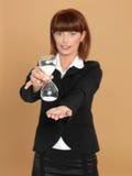 Mulher de negócios nova que prende o hourglass quebrado Imagens de Stock Royalty Free