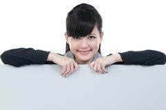 Mulher de negócios nova que prende o quadro de avisos em branco fotografia de stock royalty free
