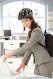 Mulher de negócios nova que sae do escritório pelo sorriso da bicicleta fotos de stock