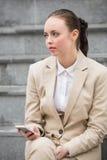 Mulher de negócios nova que senta-se em etapas Foto de Stock Royalty Free