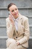 Mulher de negócios nova que senta-se em etapas no telefone Imagens de Stock