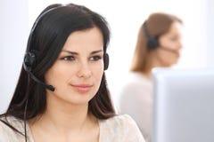 Mulher de negócios nova que senta-se na mesa e ao consultar nos clientes Serviço ao cliente e conceito do negócio imagens de stock