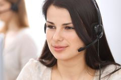 Mulher de negócios nova que senta-se na mesa e ao consultar nos clientes Serviço ao cliente e conceito do negócio foto de stock royalty free