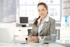 Mulher de negócios nova que senta-se no escritório brilhante fotos de stock