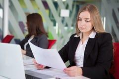 Mulher de negócios nova que senta-se no local de trabalho Imagens de Stock Royalty Free