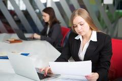 Mulher de negócios nova que senta-se no local de trabalho Fotos de Stock Royalty Free