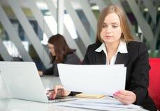 Mulher de negócios nova que senta-se no local de trabalho Fotos de Stock
