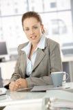 Mulher de negócios nova que senta-se pela mesa no escritório imagens de stock royalty free