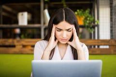 Mulher de negócios nova que sofre da dor de cabeça na frente do portátil no escritório Foto de Stock Royalty Free