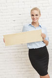 Mulher de negócios nova que sorri ao guardar a placa vazia foto de stock royalty free