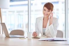 Mulher de negócios nova que sorri ao usar seu telefone no offi moderno Imagem de Stock