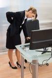 Mulher de negócios nova que tem o backpain foto de stock royalty free