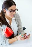 Mulher de negócios nova que trabalha em seu escritório com telefone celular Fotos de Stock Royalty Free