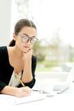 Mulher de negócios nova que trabalha em um escritório brilhante Imagem de Stock