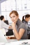 Mulher de negócios nova que trabalha no portátil no escritório imagens de stock