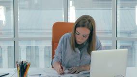 Mulher de negócios nova que trabalha no portátil no escritório moderno filme