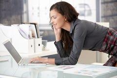 Mulher de negócios nova que usa o portátil no escritório Foto de Stock Royalty Free
