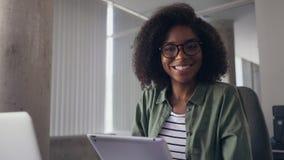 Mulher de negócios nova que usa a tabuleta digital que olha a câmera filme