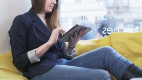 Mulher de negócios nova que usa um tablet pc video estoque