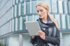 Mulher de negócios nova que verifica sua tabuleta Fotografia de Stock Royalty Free