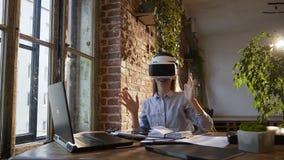 Mulher de negócios nova que veste auriculares da realidade virtual no escritório Em uma menina da classe da informática que veste