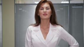 Mulher de negócios nova segura que dá os polegares acima no escritório video estoque