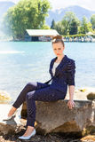 Mulher de negócios nova Sitting na grande rocha pelo lago Fotos de Stock