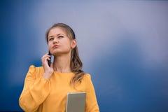 Mulher de negócios nova de sorriso no telefone que guarda a tabuleta Fotos de Stock