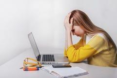 A mulher de negócios nova tem a dor de cabeça durante o trabalho Menina com portátil imagem de stock royalty free