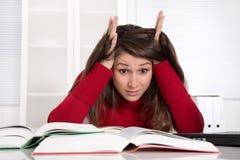 A mulher de negócios nova tem problemas da concentração no estudo ou em fotografia de stock