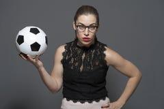 Mulher de neg?cios nova virada - fan de futebol que guarda a bola de futebol preto e branco nas m?os imagem de stock