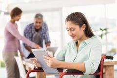 Mulher de negócios ocasional na cadeira de rodas usando a tabuleta Fotos de Stock Royalty Free